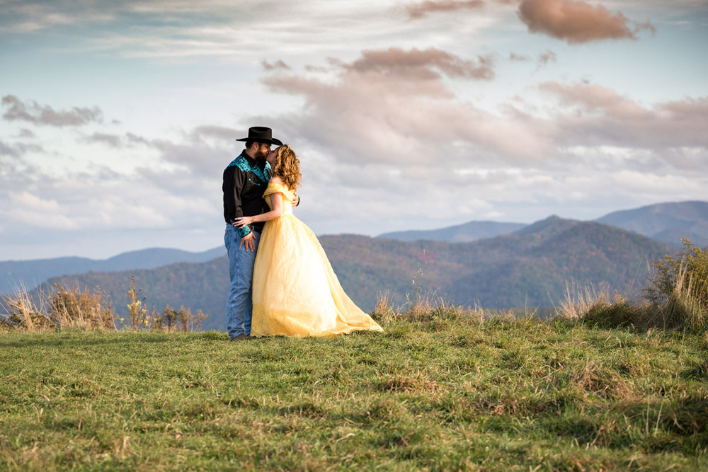 bride in yellow dress kisses her groom under blue skies against fall colored mountains