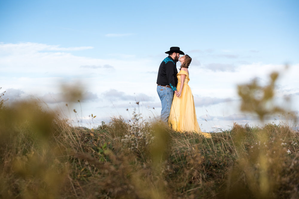 bride and groom in a delicate kiss in tall grass against a blue sky