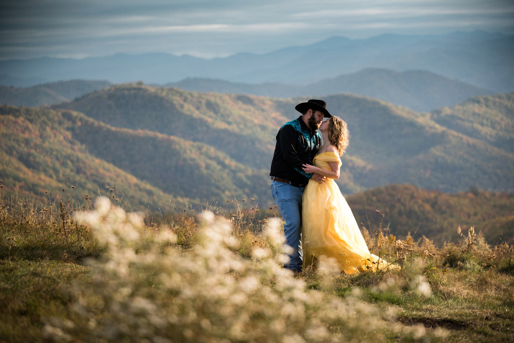 groom pulls in his bride in yellow dress for a kiss