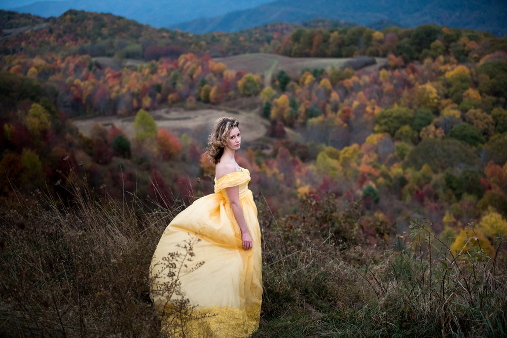 wind catches a brides yellow dress in a valley of fall color