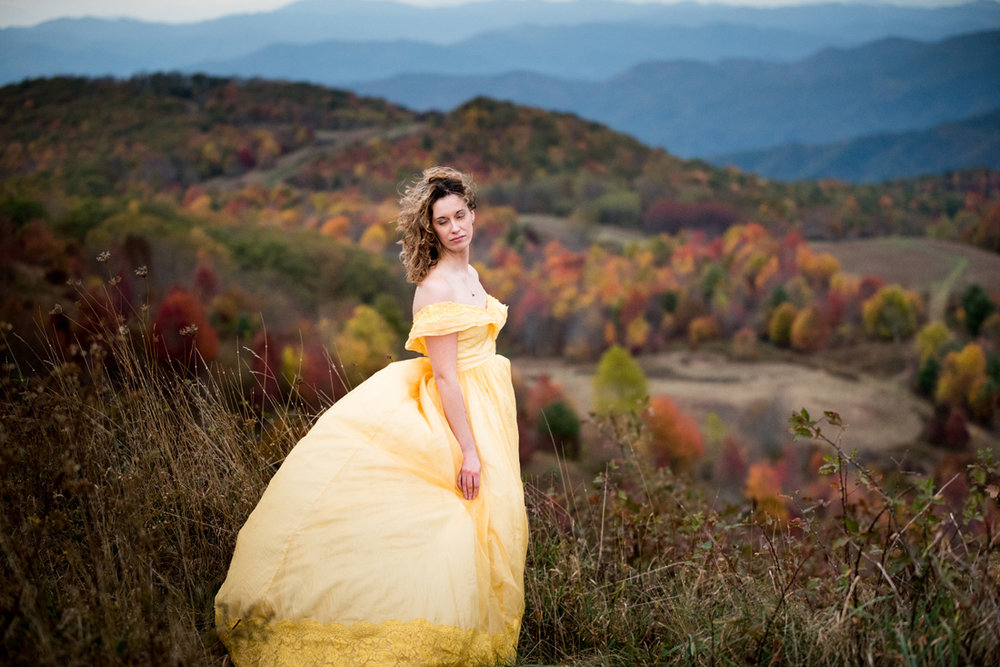 bride in yellow dress surrounded by fall color in the mountians