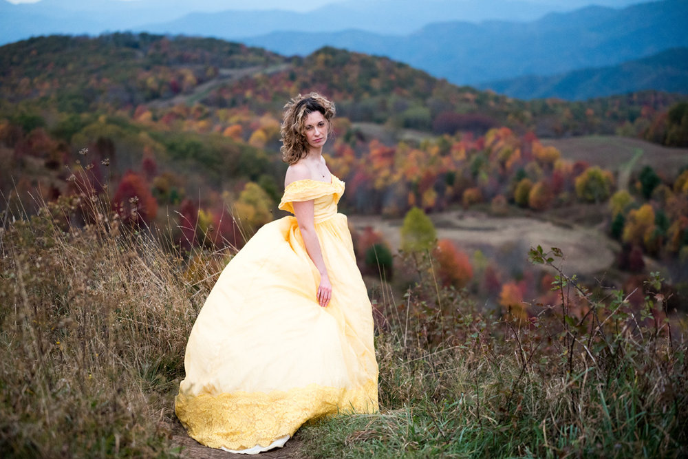 bride in yellow dress above a valley of fall color and blue ridge mountians