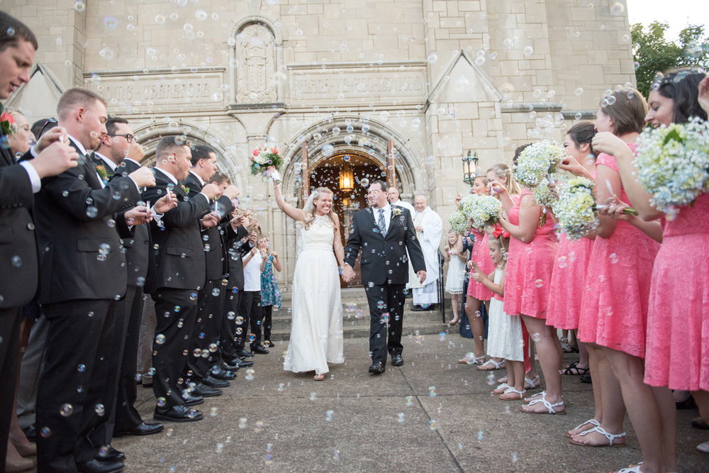 Bride holds her bouquet high, holding the groom's hand as they walk through thousands of bubbles.