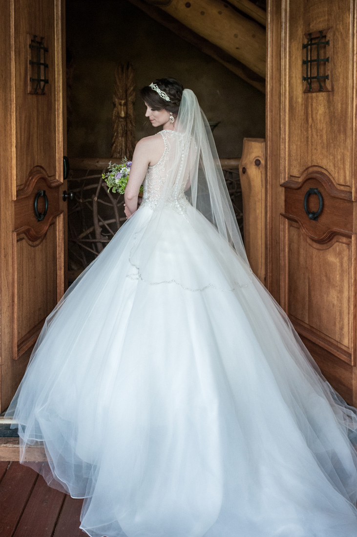 Bride gently looks over her shoulder as she heads through a set of stately doors.
