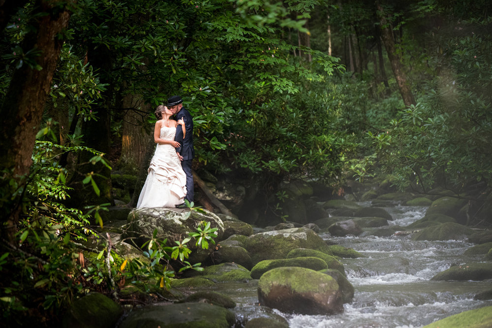 Bride and groom beside a mountain stream.