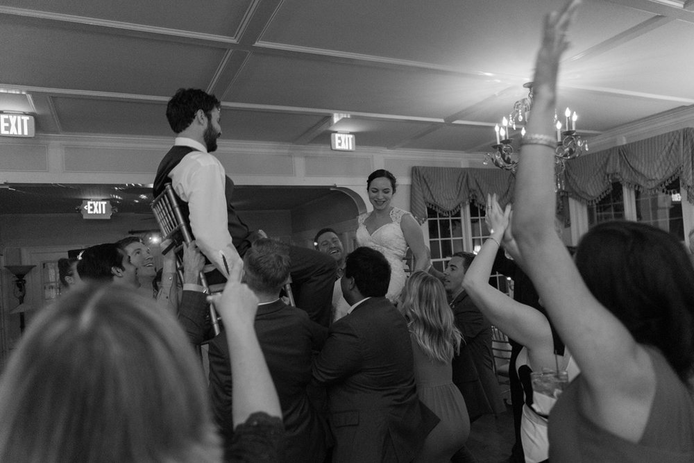 "Bride & groom celebrate the Jewish tradition the ""Hora"" being lifted into the air in chairs!"
