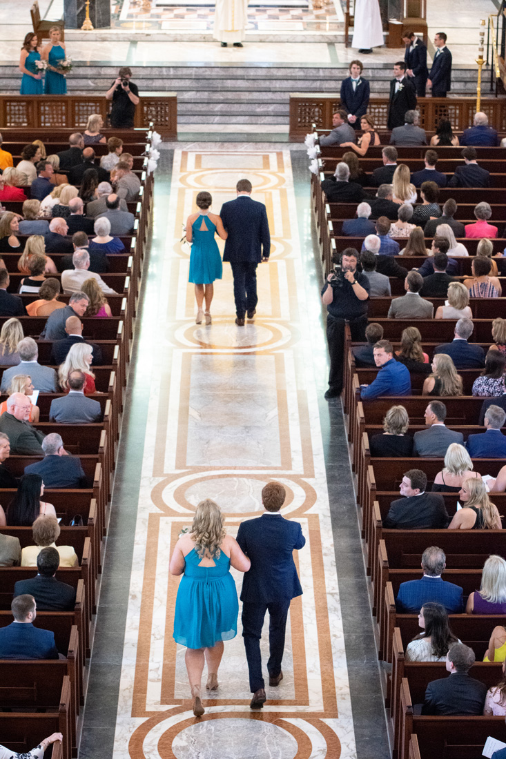 Beautiful bridesmaids escorted down the long cathedral aisle.