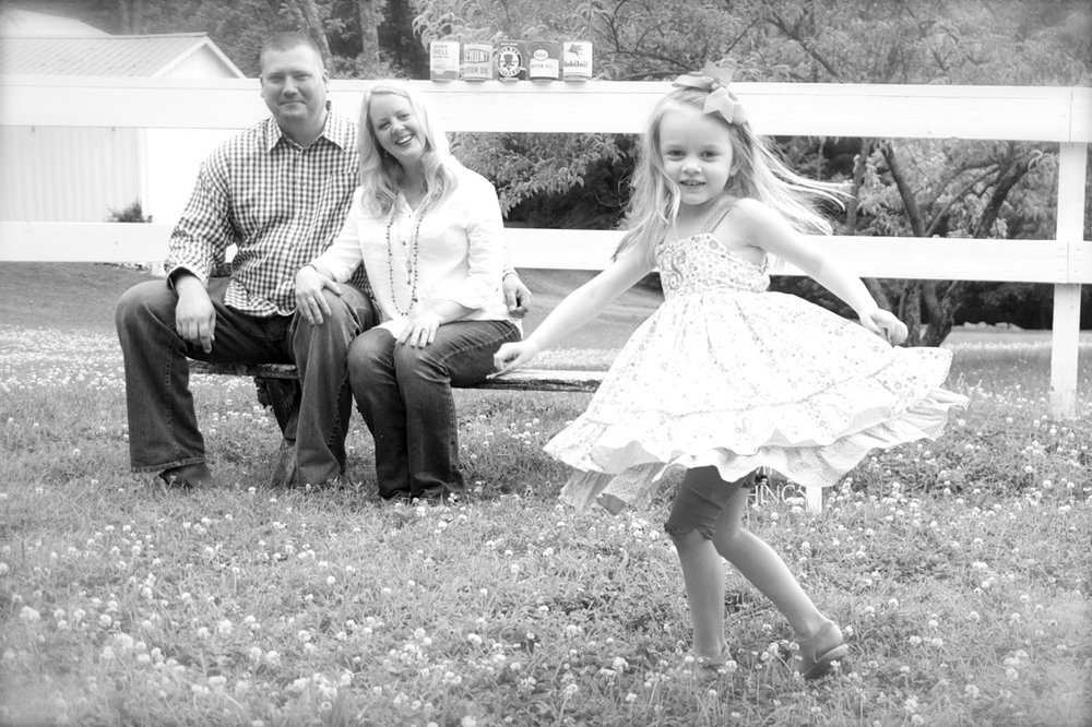 Family photo with dancing little girl as momma & daddy watch