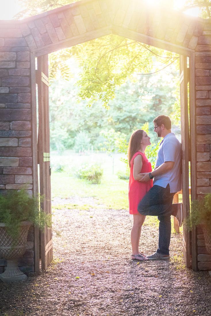 engaged couple standing beneath golden sunight