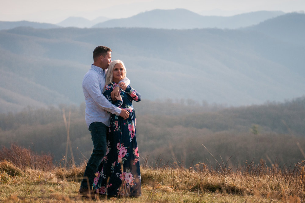 engaged couple leans into one another high in the mountians