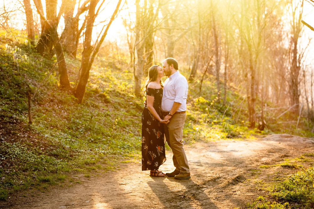 engagement photo of engaged couple walking along a path in golden sunlight