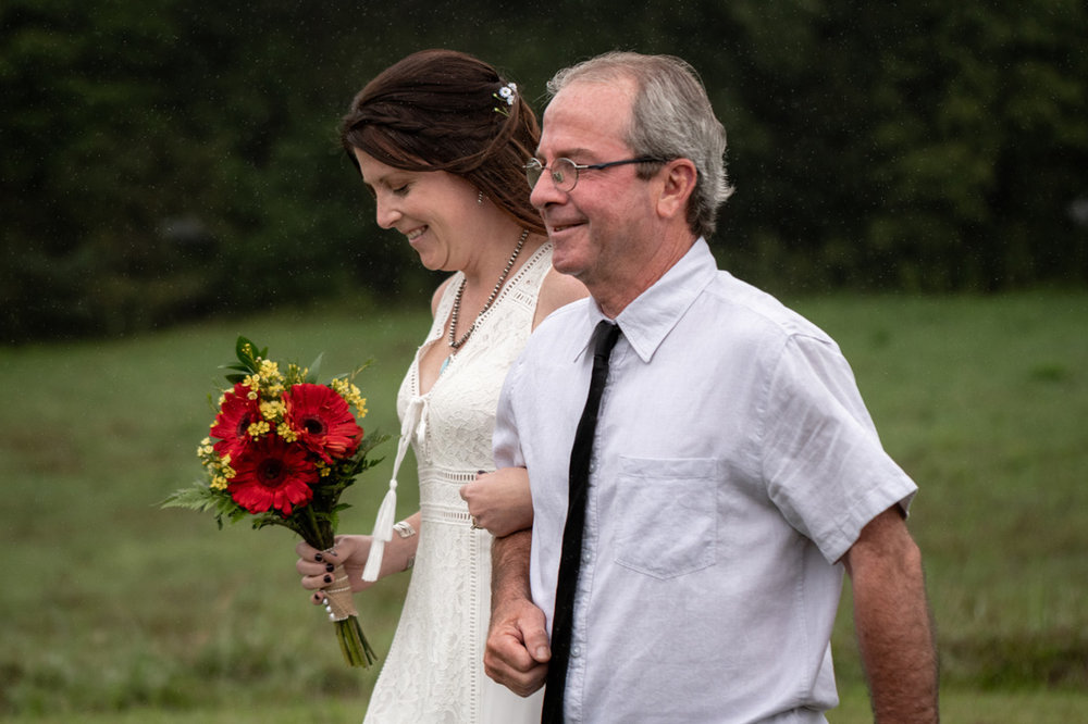 Father of the bride is all smiles as they ditch the umbrella!