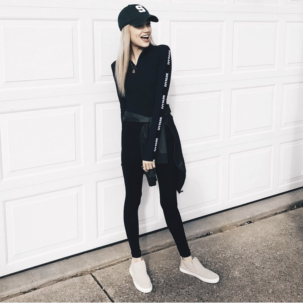 Ivy Park bodysuit, Tory Burch pendant, Under Armour jacket, Nike leggings and Dolce Vita sneakers.