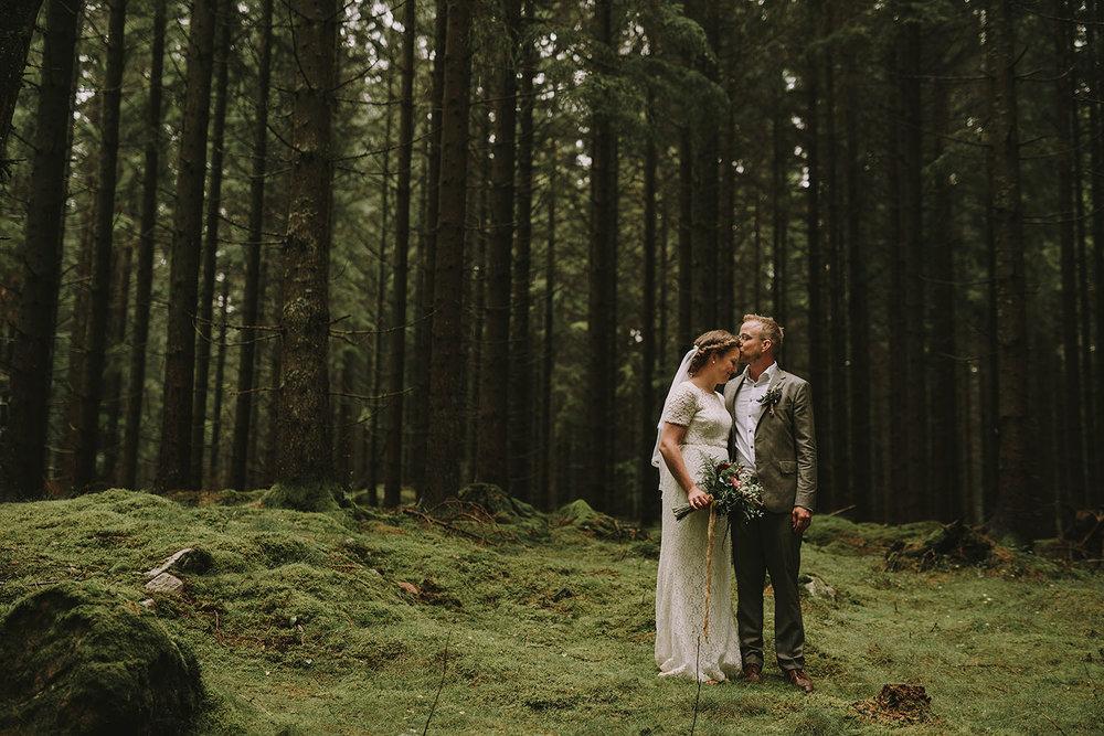 Brudpar med bohemisk stil på sin bröllopsdag i granskog i Hylte