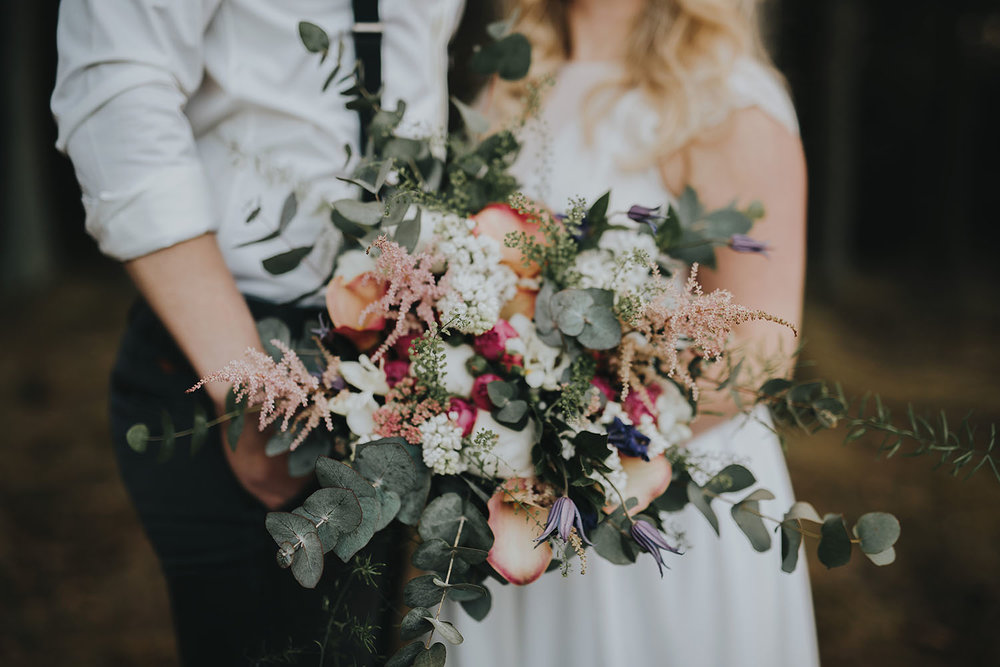 Bröllopsfotografering i skogsmiljö i Hylte med vild brudbukett