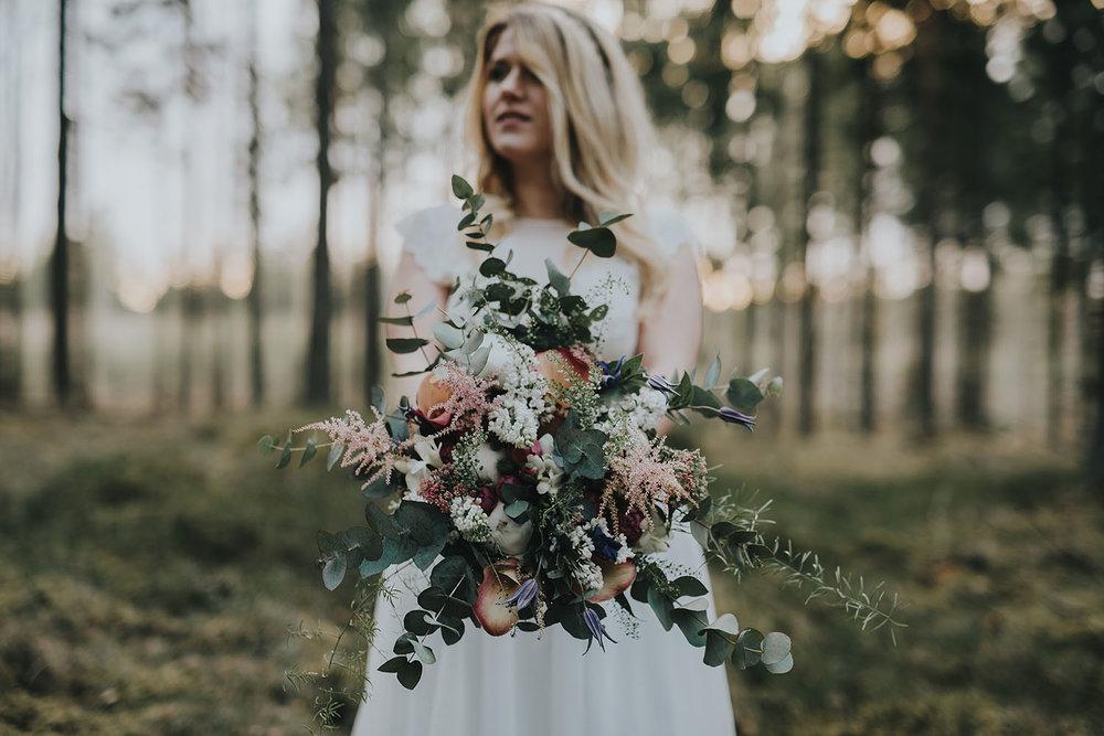Brud med vild brudbukett i skogsmiljö under fotografering av bohemiskt bröllop i Halmstad