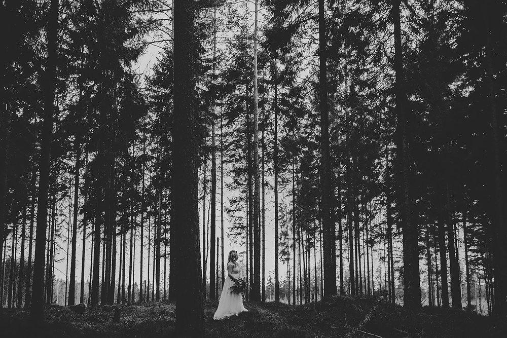 Brud med bröllopsklänning i spets och vild bukett i skogsmiljö