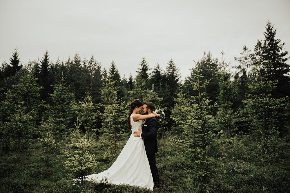 Brudpar under fotografering med bröllopsfotograf i granskog