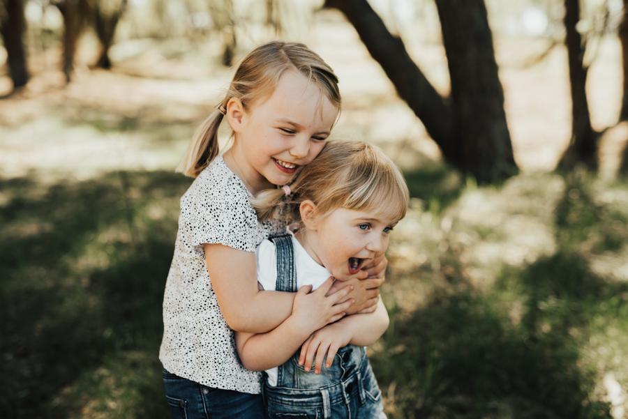 Varm kram av syskon under familjefotografering i Halmstad