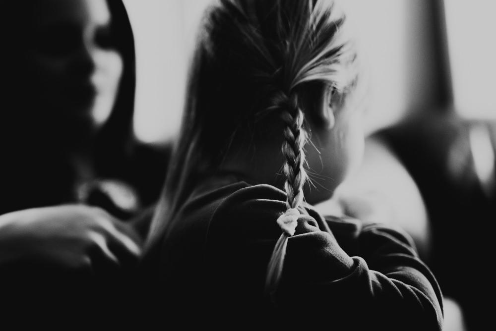 Flätar håret under familjefotografering lifestylefotograf i Halmstad