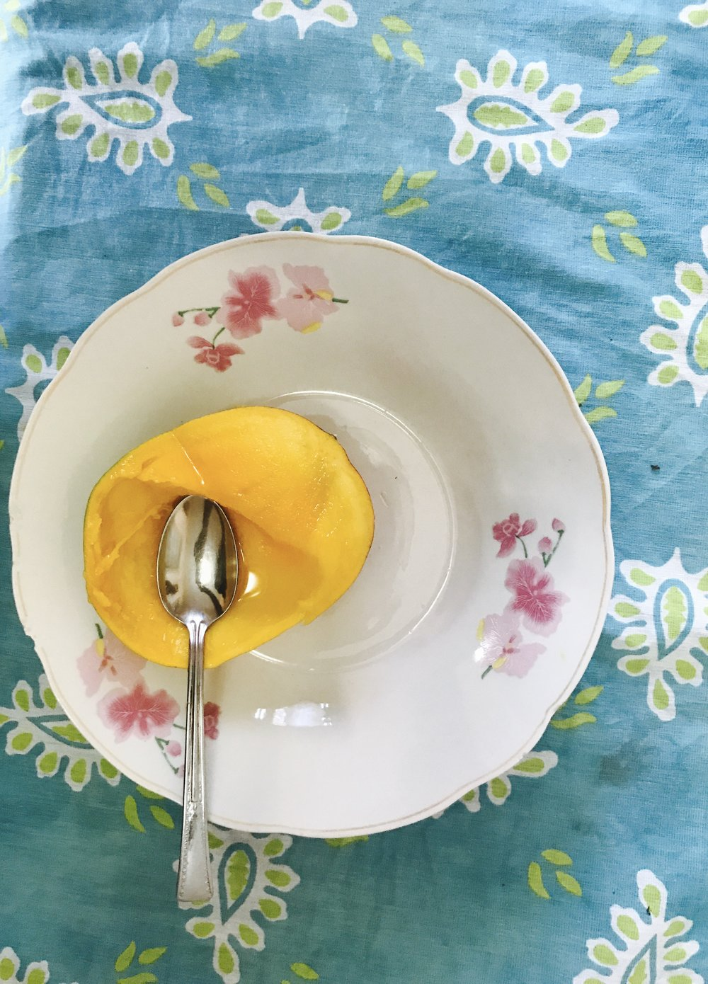 Enjoying a mango - with a spoon for the first time.