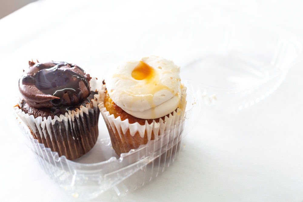 A chocolate cupcake and a vanilla Cupcake with caramel buttercream dried with caramel.