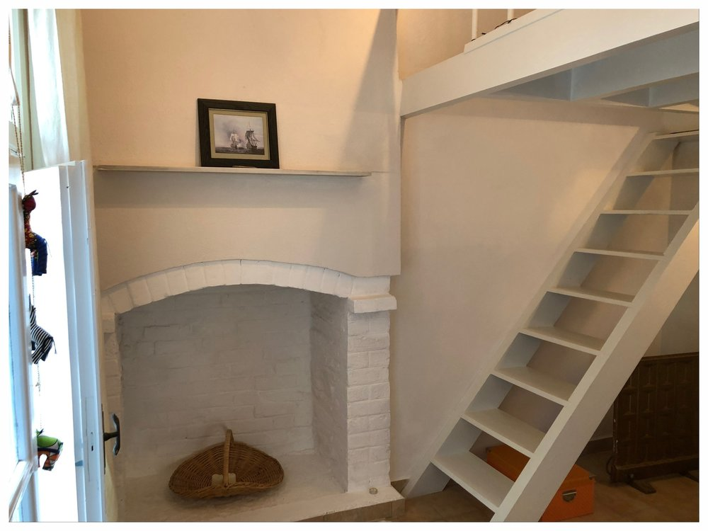 Bedroom with fireplace detail, staircase to platform bed