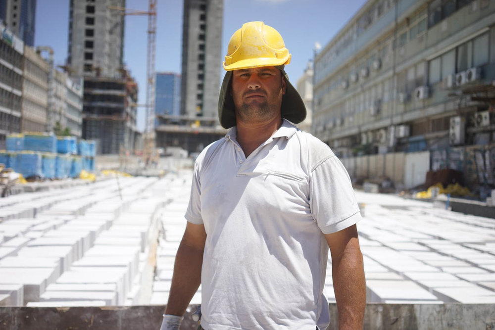 Tel Aviv, people in the city, builder with a yellow helmet
