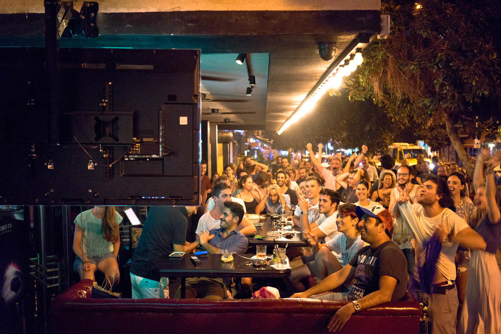 Tel Aviv, people in the city, watching sports in a bar, happy faces