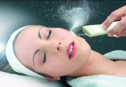 """Ultrasound Facial   This high-tech facial exfoliates and empties your pores of debris through cavitation. It penetrates deeply highly active ingredients through sonophoresis and activates fibroblast cells responsible for collagen and elastin growth. Customized for your specific skin type.   Benefits Of Ultrasound Facial   Acne: Sometimes the body can become immune to certain acne medications if used over an extended period of time. Regular ultrasound therapy keeps the acne away long after other expensive medications and treatments. Ultrasound gently cleanses the skin of acne-causing bacteria and unwanted toxins while making the skin more receptive to acne lotions, creams and other skin treatment products. The results can be extremely dramatic - even after only a few treatments.  Enlarged Pores: With regular use, ultrasound therapy can be very effective at reducing the size of enlarged pores, softening skin and controlling excess sebum production. The gentle spray of oxygen molecules produced by the high frequency, diminishes enlarged pores by penetrating deep down into the root of the affected area and cleaning out unwanted debris and toxins allowing the pore to quickly regain its natural size once again.  Fine Lines, Wrinkles, Sagging Skin: The action of ultrasound therapy increases blood circulation, which in turn nourishes the skin's surface and renews underlying cells. It also produces an enriched form of oxygen, which provides the skin with a firm, youthful, vibrant glow. It diminishes the appearance of fine lines and wrinkles, tightens double chins and jowls and improves overall skin texture and tone by promoting increased collagen production.  Puffy Eyes: The """"oxygenation"""" action produced by ultrasound aids in lymphatic drainage and disperses excess fluid while increasing blood circulation. The result is a reduction in the appearance of congested, tired, puffy eyes.  Dark Eye Circles:Scientific research has shown the cause of severe dark eye circles to be bro"""