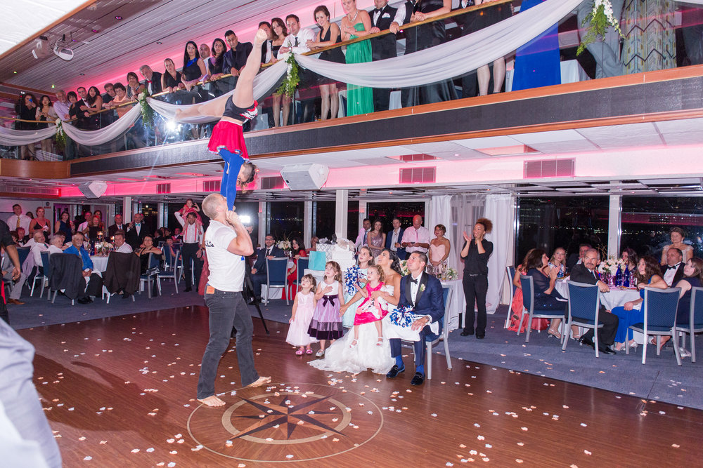 Bride, Groom and guests all around in awe of our Acro Duo performing in the 2 tiered ballroom of a Boat!   Wedding Venue: Hornblower Infinity New York