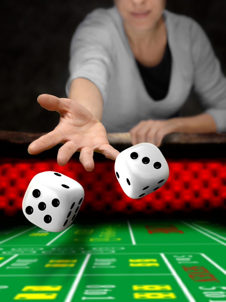 Woman throwing dice at a craps table