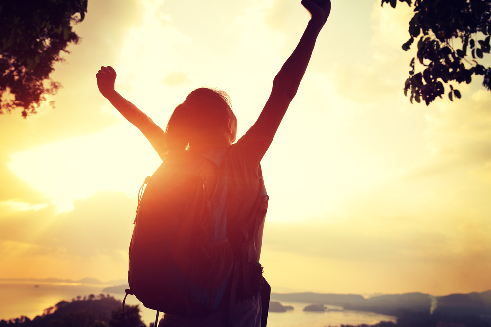 Woman wearing backpack looking at the sun rise with arms raised in the air