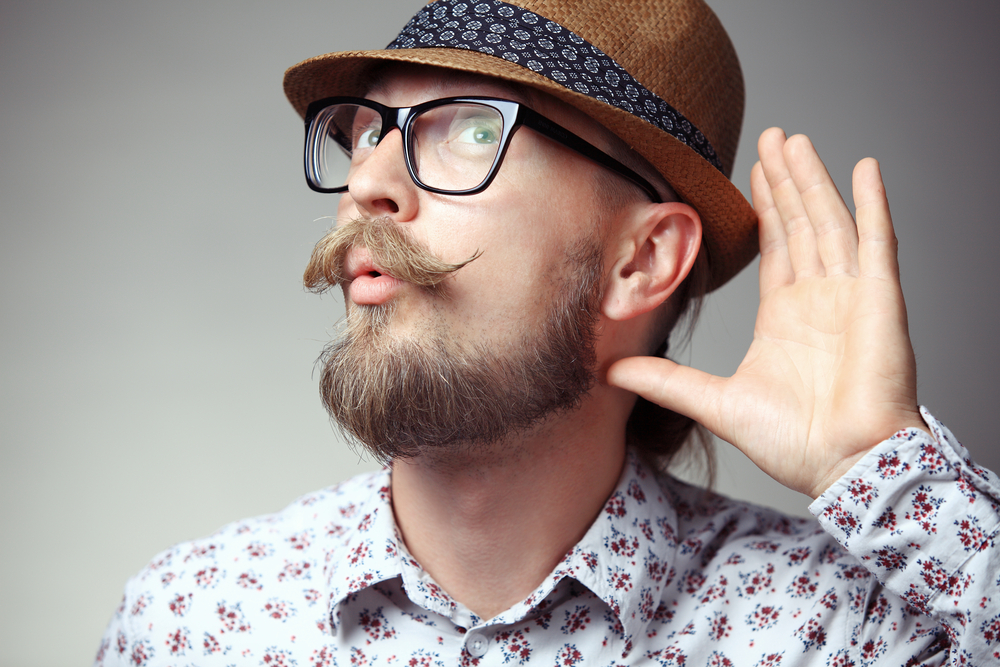 Man in hat with hand up to ear to hear better