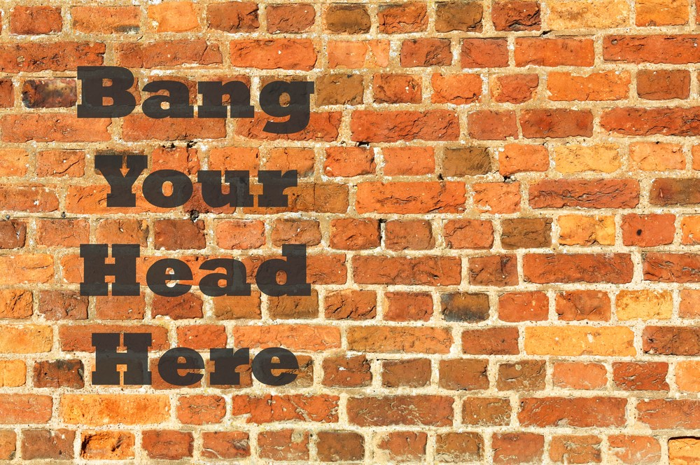 """Brick wall with the text """"Bang your head here"""" written on it."""