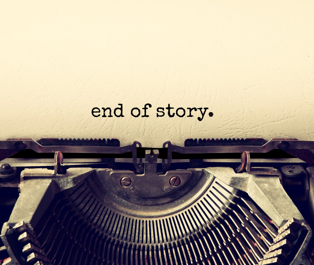 """An old typewriter with the words """"end of story."""" typed on to the page."""