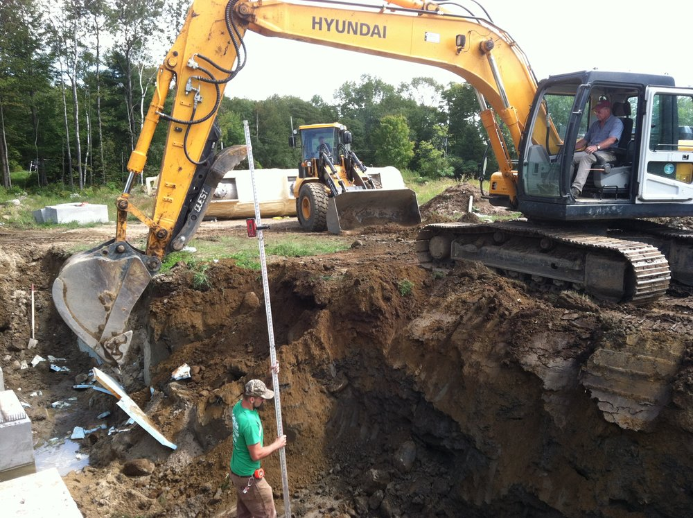 Digging hole to re-bury hot water storage tank.  Note excavator sitting on area of last year's garlic beds.