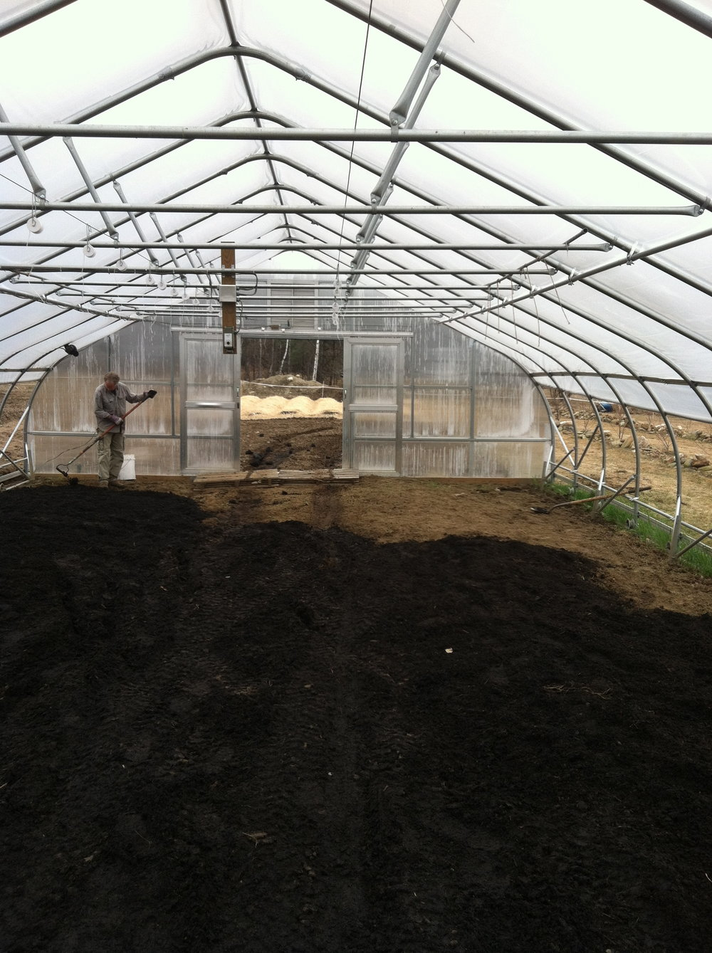 Raking out biochar/compost mix in rolling greenhouse.