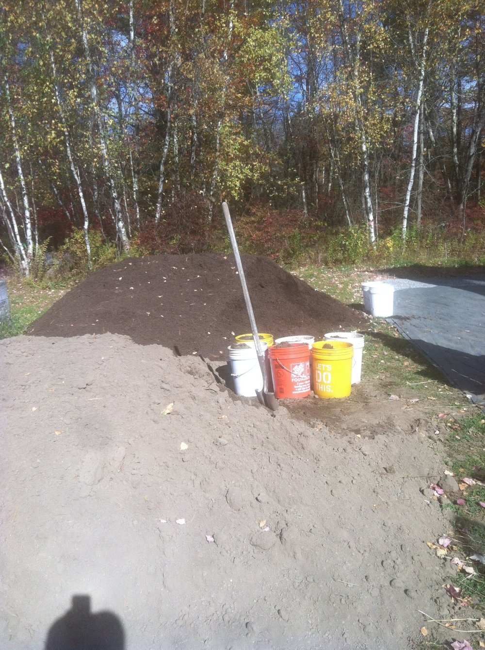 Loam and compost piles outside the seedling greenhouse.