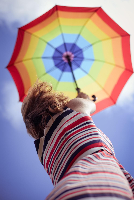 Picture of elegant romantic woman having fun holding up umbrella