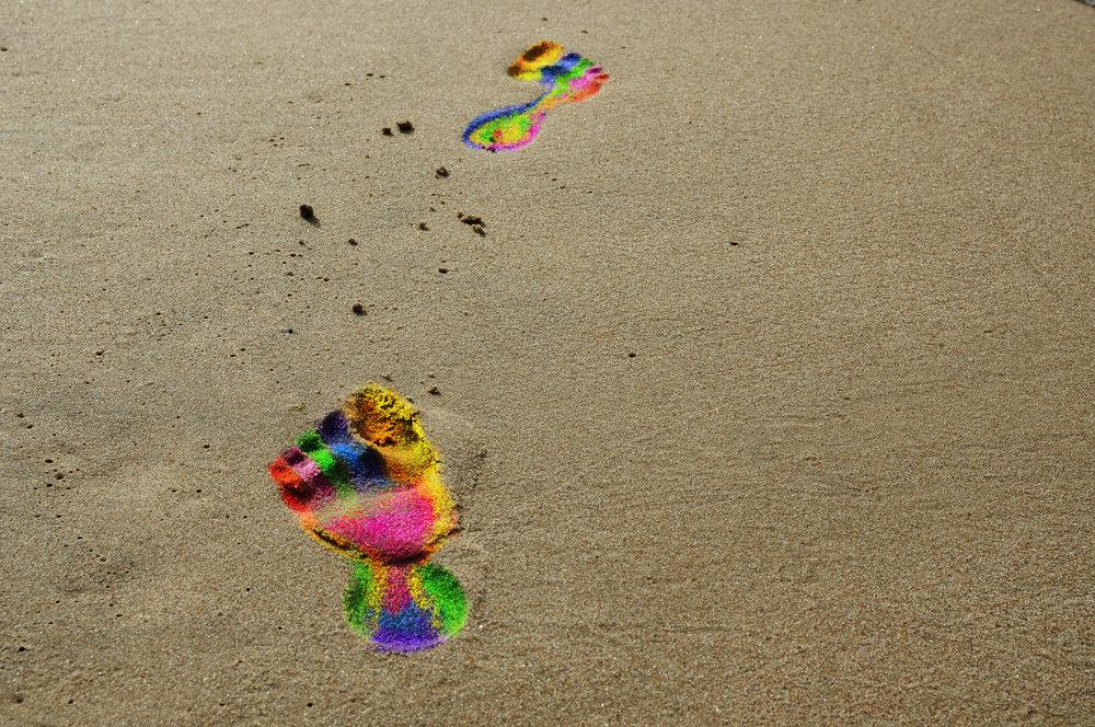 Ślady stóp w kolorach tęczy na plaży.