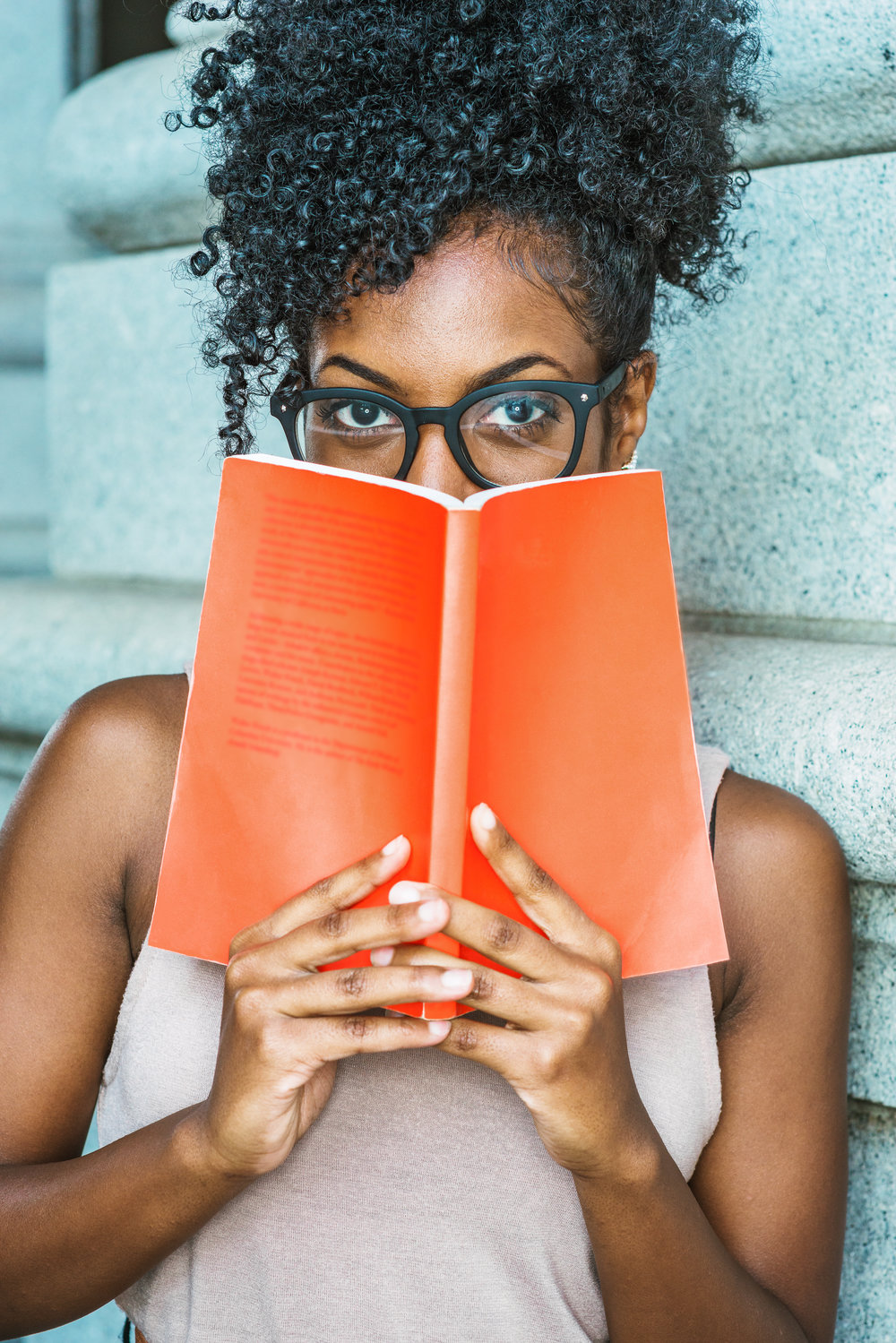Reading and Thinking. Young African American female college student with afro hairstyle, wearing glasses, standing outside by column in New York, holding red book, covering face, looking, thinking..