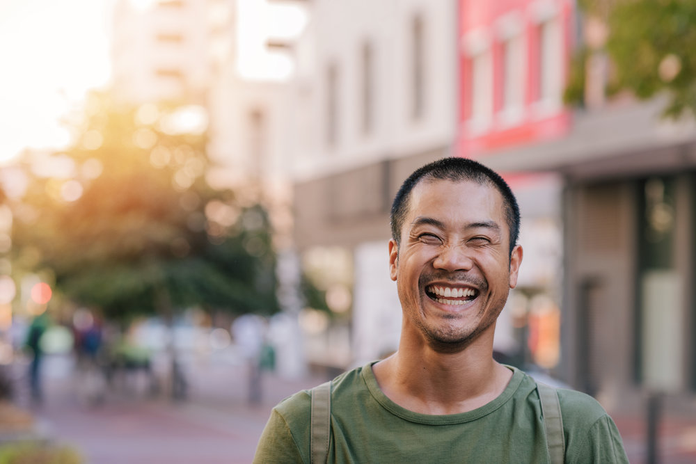 Young Asian man standing on a city street laughing