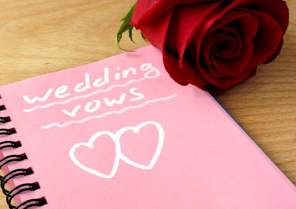 Pink notepad with wedding vows and rose on a wooden background.