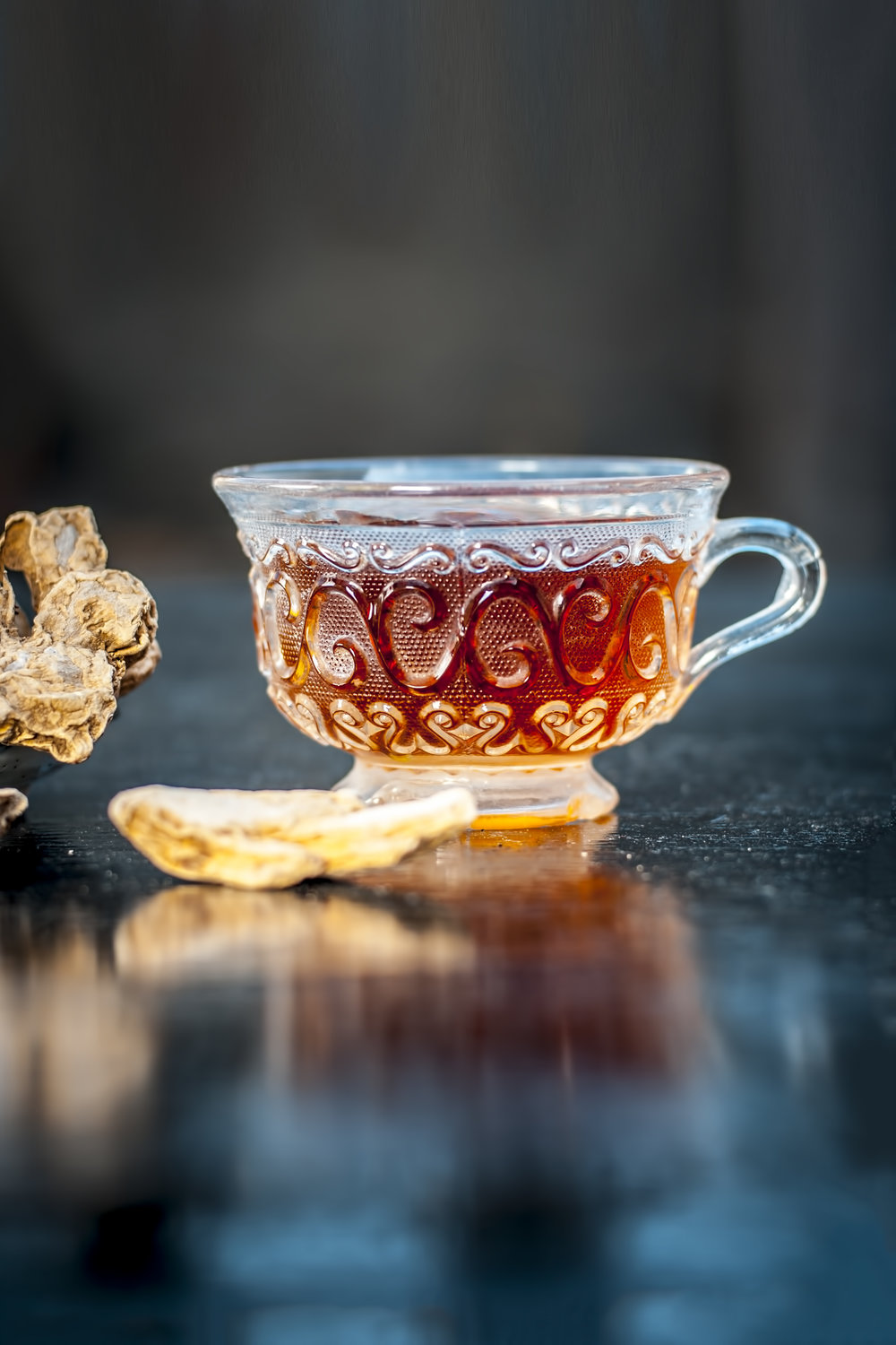 Beneficial tea of dried ginger or Zingiber officinale with benefits like help digestion, reduce nausea and help fight the flu and common cold in transparent cup with raw dried ginger.