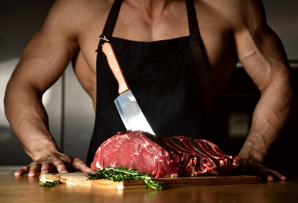 Strong sport man prepare cook beef steak ribs on dark kitchen background healthy eating concept on black