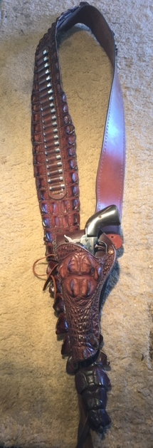 "The Crocodile Bandolier, with the head of the croc on the holster. The tail of the baby croc hangs down below the bottom of the holster, which hangs off the bandolier with a 2"" belt passing through two slots, so the two-tongue buckle is moved in behind the holster loop. Cost, $1,495 with safe dummy nickel bullets -- they have no powder, no primer. Call Colin  818 889-6988  or cell  818 309-8125  for any custom work."
