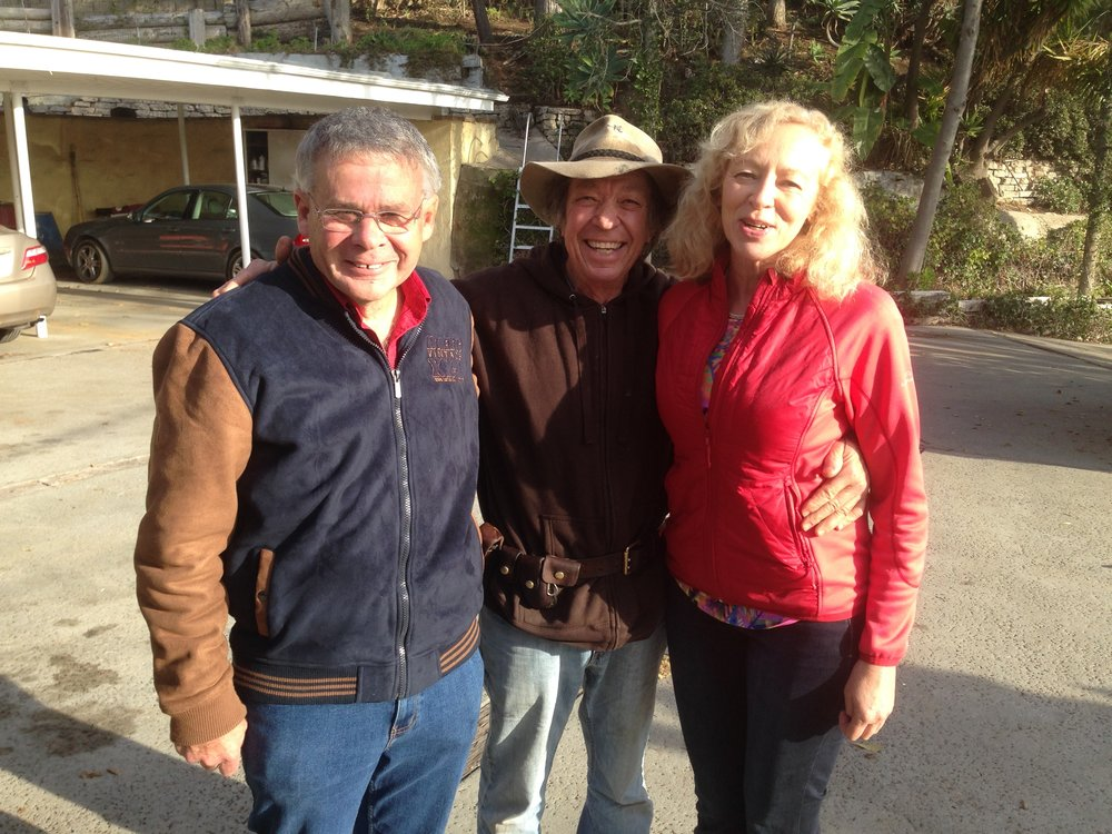 "COLIN VISITS WITH NEIL AND HIS WIFE CHRIS, ON COLIN'S RANCH IN MALIBU . THEY ALL MET 30 YEARS AGO WHEN COLIN FIRST STARTED PESTERING NEIL ABOUT WRITING A BOOK. COLIN DIDN'T BUY NEIL'S EXCUSE THAT HE WAS NOT A WRITER. AFTER WORKING AT IT FOR A COUPLE OF YEARS, NEIL DISCOVERED HE WAS INDEED A WRITER AND TODAY HE HAS A RUNAWAY BEST SELLER!! RECALLS CHRIS: ""COLIN, THERE WERE TIMES I WANTED TO KILL YOU! WRITING THIS BOOK WAS DRIVING US CRAZY. BUT NOW I JUST WANT TO HUG YOU FOR MAKING US DO IT. """