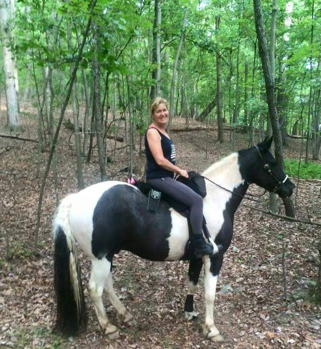 Kristina Fender in the woods on her Gypsy Vanner cross Little Joe