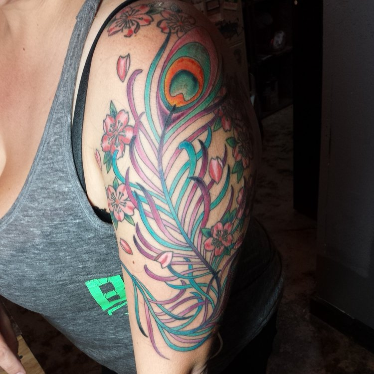 Peacock Feather Plume and cherry blossoms in color. Half sleeve upper arm tattoo.